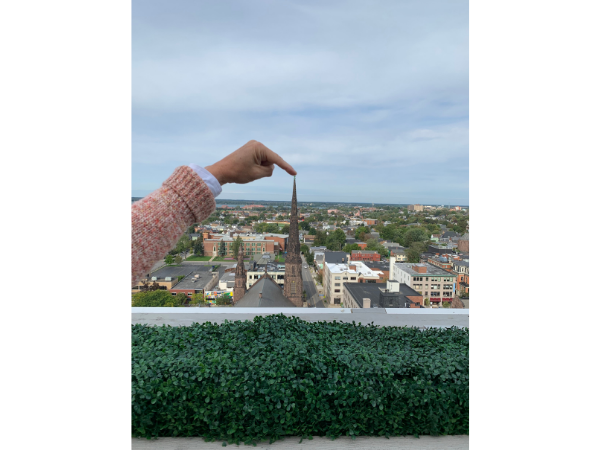 Aerial view of Buffalo with St. Louis in view and a woman's arm in view to make it look like she's touching the top of the church's steeple