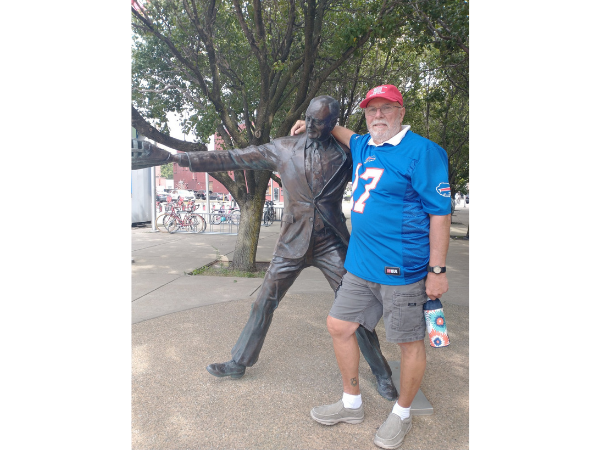 man standing with a statue of Mayor Jimmy griffin outside Salen Field in Buffalo, NY