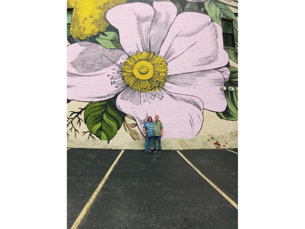 A couple standing in front of a large flower mural in Downtown Buffalo